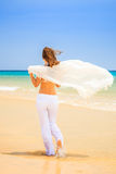 Young woman on ocean beach. Young woman in white walking on ocean beach Stock Image