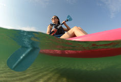 Young woman on ocean in kayak. Youg woman wearing life vest in pink kayak royalty free stock photo
