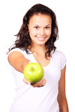 Young woman offering an apple. Young woman offering a green apple isolated on white background Royalty Free Stock Photos