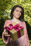 Young woman offering gift box Stock Photos