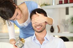 Young woman offering surprise-gift. Young women offering surprise-gift to her boyfriend Stock Images