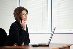 Young woman in office. Young woman in black dress in office royalty free stock image