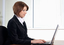 Young woman in office. Young woman in black dress in office stock photo