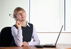 Young woman in office. With laptop royalty free stock image