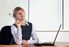 Young woman in office. With laptop and glasses royalty free stock image