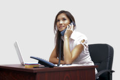 Young woman at the office. Young woman talking at the telephone in the office Stock Photography