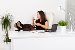 Young woman in the office. Young woman drinking coffee in the office Royalty Free Stock Photo