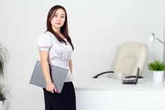 Young woman in the office. Young woman stand at a table in the office Stock Photo