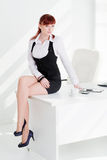 The young woman in office. The young woman sits on a table at office stock image