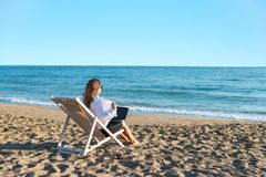 Young woman in office clothes with a laptop on the beach on a background of the sea in a summer sunny day. Concept. Young woman in office clothes with a laptop stock image