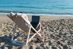 Young woman in office clothes with a laptop on the beach on a background of the sea in a summer sunny day. Concept. Young woman in office clothes with a laptop royalty free stock photography