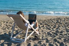 Young woman in office clothes with a laptop on the beach on a background of the sea in a summer sunny day. Concept. Young woman in office clothes with a laptop royalty free stock photos