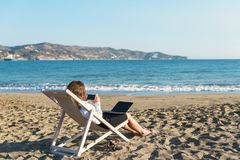 Young woman in office clothes with a laptop on the beach on a background of the sea in a summer sunny day. Concept. Young woman in office clothes with a laptop royalty free stock photo