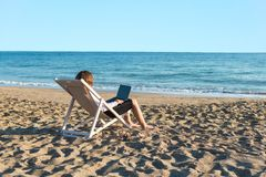 Young woman in office clothes with a laptop on the beach on a background of the sea in a summer sunny day. Concept. Young woman in office clothes with a laptop royalty free stock image