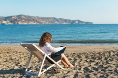 Young woman in office clothes with a laptop on the beach on a background of the sea in a summer sunny day. Concept. Young woman in office clothes with a laptop stock images