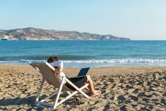 Young woman in office clothes with a laptop on the beach on a background of the sea in a summer sunny day. Concept. Young woman in office clothes with a laptop stock photography