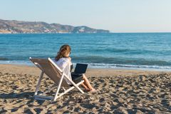 Young woman in office clothes with a laptop on the beach on a background of the sea in a summer sunny day. Concept. Young woman in office clothes with a laptop stock photos