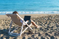 Young woman in office clothes with a laptop on the beach on a background of the sea in a summer sunny day. Concept. Young woman in office clothes with a laptop stock photo