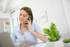 Young woman at the office discussing on the phone Stock Image