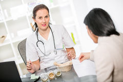 Young woman in an office at the doctor homeopaths. Royalty Free Stock Image