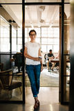 Young woman at office doorway holding a coffee Royalty Free Stock Photos