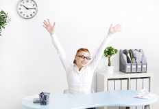 Young woman in the office with hands in the air. Stock Photos