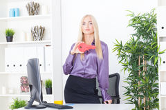 Young woman at office holds big a red key Royalty Free Stock Photography