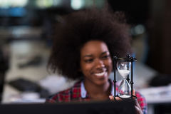 Young woman at office looking at sand  clock Royalty Free Stock Images