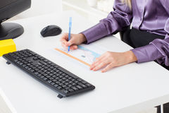 Young woman at office makes a financial chart Stock Photo