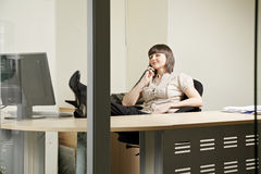 Young woman in office on phone Stock Photos