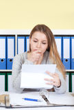 Young woman at office reading a letter Royalty Free Stock Photography
