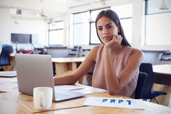 Young woman in office using laptop computer looks to camera Royalty Free Stock Image