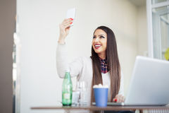 Young woman in office using mobile phone Stock Photography