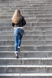Young woman with old camera steps upstairs Royalty Free Stock Photo