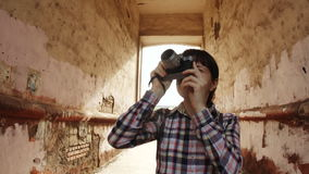 A young woman with an old camera takes pictures through an old arch stock footage