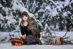 A young woman in old clothes is sitting with brushwood and a basket with apples in the snow in the winter forest Stock Photo