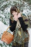 A young woman in old clothes is standing with a basket and brushwood in the snow in the winter forest. Royalty Free Stock Photos