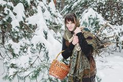 A young woman in old clothes is standing with a basket and brushwood in the snow in the winter forest. Royalty Free Stock Photo