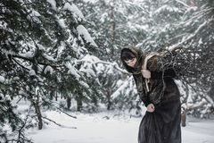 A young woman in old clothes stands with brushwood in a winter forest. character from the fairy tale. A young woman in old clothes stands with brushwood on snow Stock Photo
