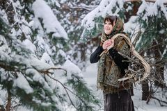 A young woman in old clothes stands with brushwood in a winter forest. character from the fairy tale. A young woman in old clothes stands with brushwood on snow Royalty Free Stock Images