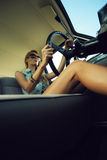Young woman in an old fashioned car Stock Images