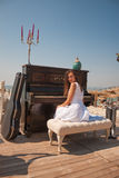Young woman, old piano Royalty Free Stock Image