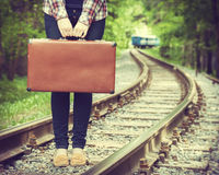 Young woman with old suitcase on railway. Departing train on background, retro stylized Royalty Free Stock Photo