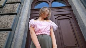 Young woman in the old town. Angle from the bottom point. The girl turns around and fixes her hair stock footage