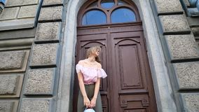 Young woman in the old town. Angle from the bottom point. The girl turns around and fixes her hair stock video