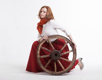 Young woman with an old wagon wheel Royalty Free Stock Image