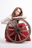 Young woman with an old wagon wheel Stock Photography