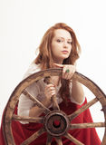 Young woman with an old wagon wheel Stock Images
