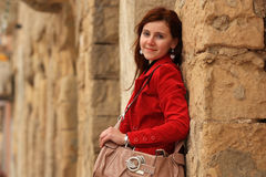 Young woman and old wall. Image pfa  young slavic woman wearing red jacket standing against old honey colored wall Royalty Free Stock Photos