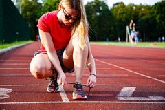 Free Young Woman On Running Track Lacing Her Shoes Royalty Free Stock Image - 162093336